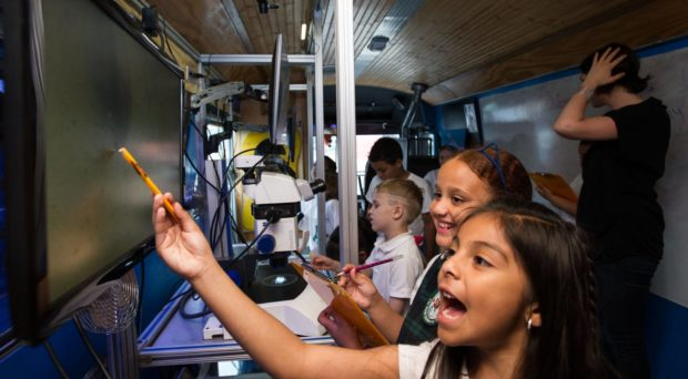 Students aboard the BioBus find microorganisms under the microscope.