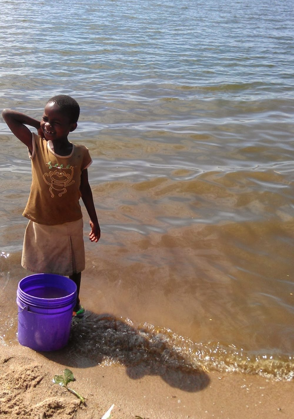 Little girl collecting water from an open water source - Access to safe water is crucial for disease prevention. Copyright Anouk Gouvras