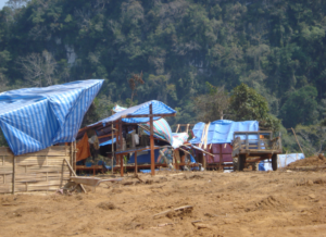 Land clearing for road construction project in northern Lao PDR: temporary worker shelters near to forested areas