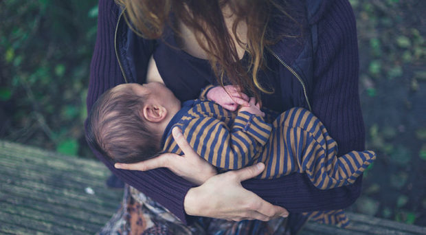 A young mother is breastfeeding her baby in a forest