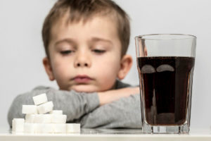A young child rests their chin on their arms looking at a pile of sugar cubes and a glass of a carbonated cola drink on a table
